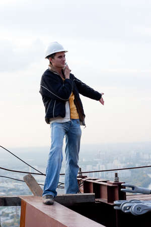young contractor stay on a roof of a high building, calling by phone photo