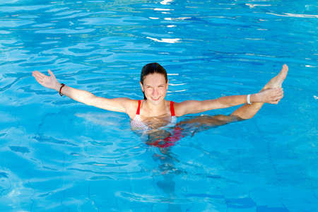 water aerobics: Woman get Stretch in water pool. Holds the foot Stock Photo