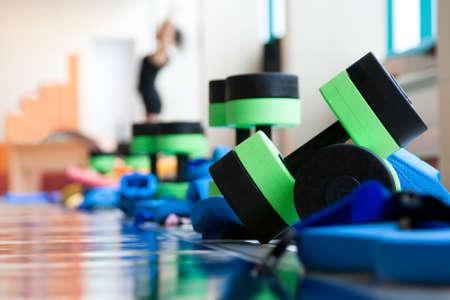 equipment for aqua aerobics on pool side. woman stretching on background