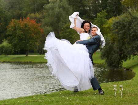 Bruid en bruidegom buiten op het gazon met champagne Stockfoto