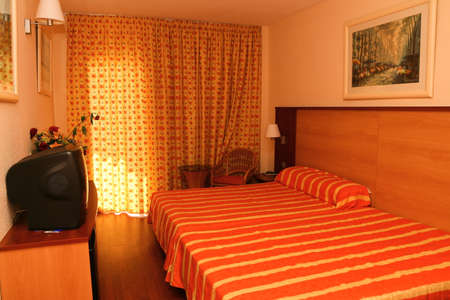 nice accommodations: Colorful bedroom in hotel with table and lampshades and window