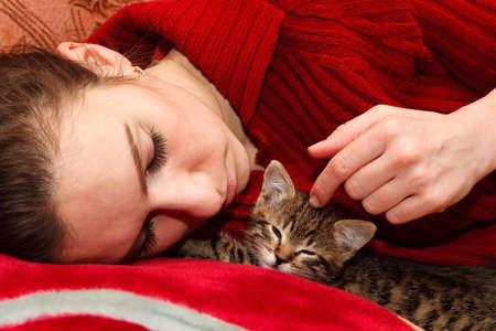 jonge vrouw slapen op bed met kitten