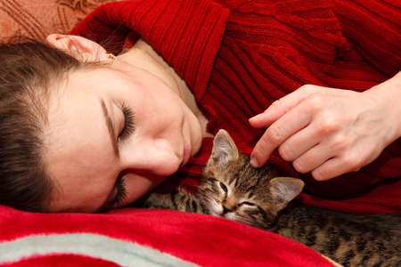 cat sleeping: young woman sleeping on bed with kitten