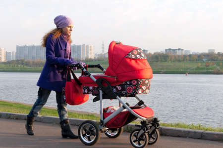Young mother with a baby carriage walking in park photo
