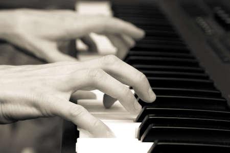 handen van toetsenist op toetsen van de synthesizer. zwart en wit