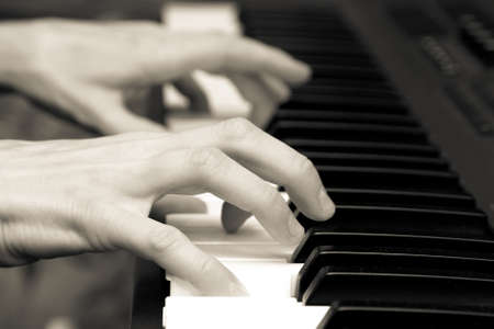 hands of keyboard player on keys of synthesizer. black and white