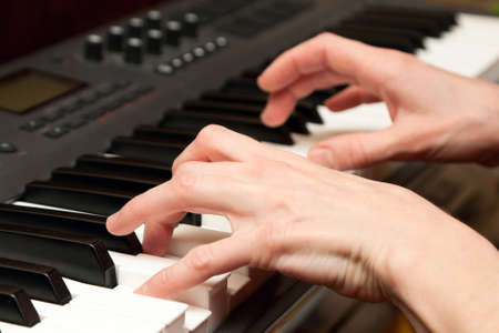 hands of keyboard player on keys of synthesizer photo