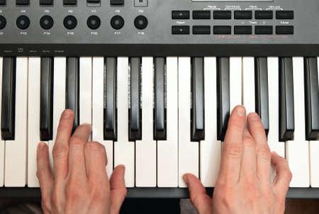 teaching music: hands of keyboard player on keys of synthesizer