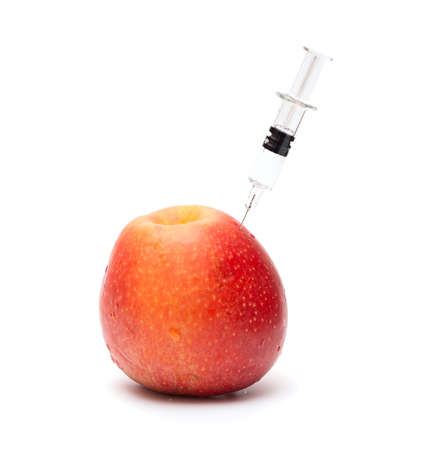 Syringe with liquid entered into red yellow apple  GMO Stock Photo - 13409303