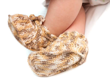 bootees: newborn feet in crocheted bootees on white