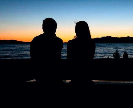 silhouette of a loving couple sitting on a bench at sunset photo