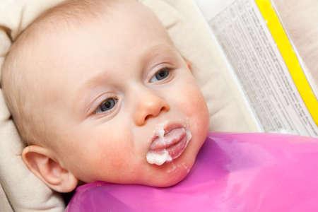 lengua afuera: hermoso niño comer una papilla y puesto en la lengua Foto de archivo