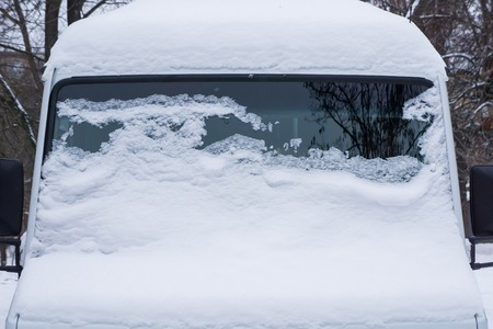 The windshield of the frozen minibus is covered with ice and snow on a winter day. Stock Photo