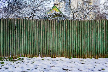 Old green wooden stockade. Fence around the house