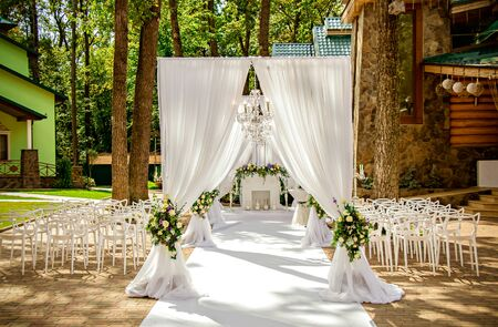 Place for wedding ceremony in white color ,with white fireplace and chandeliers decorated with flowers and white cloth and wooden chairs for guests on each side outdoors. Stockfoto