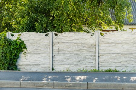 A fence made of grey concrete blocks with decorative greenery Banque d'images