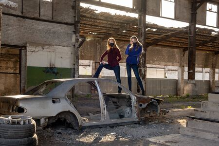 Two young girls in black masks in a destroyed building near the remains of a car. Consequences of the Apocalypse, epidemic, destruction.