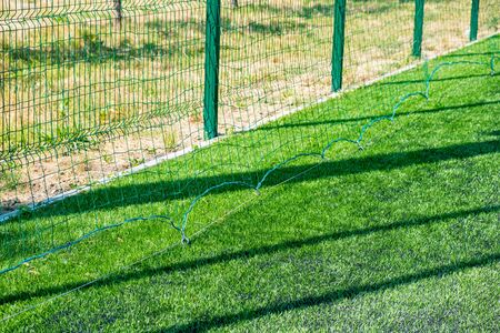 Green protective grid close-up. The pattern of a protective grid for a sports ground. Sports background.