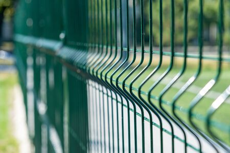 Steel grating fence of soccer field,Metal fence wire with grass in the background.