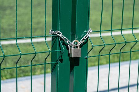 Rusty lock on the gate. Entrance to the football field. Metal fence wire with grass in the background.