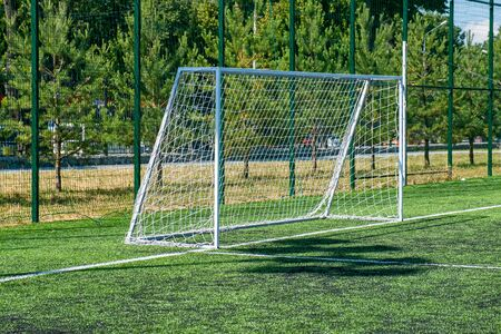 Football goal at the stadium. Metal fence wire in the background.
