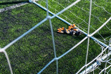 Goalkeeper gloves are on the grass near the football goal.