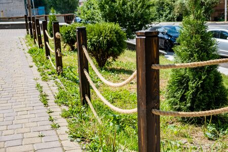 A small decorative fence . fence made from wooden poles and ropes.