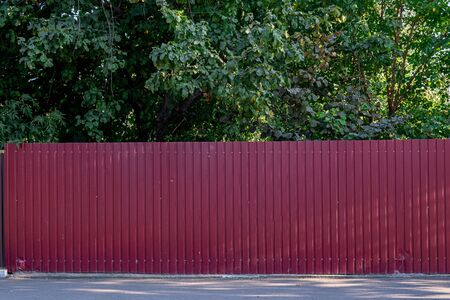 Fence made of panels of red corrugated sheet metal with asphalt in front and trees behind it.