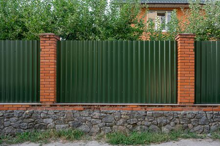 Fence made of panels of green corrugated sheet metal with grass in front and trees behind it
