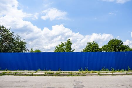 Blue corrugated iron fence against blue sky with clouds.