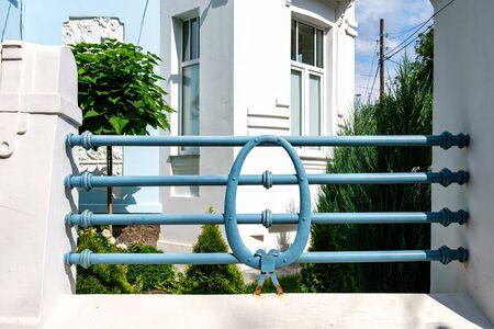 Metal decorative blue fence near the house.