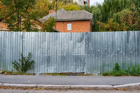 Silver metal corrugated fence on the background of a residential building. The texture of profiled metal. Standard-Bild