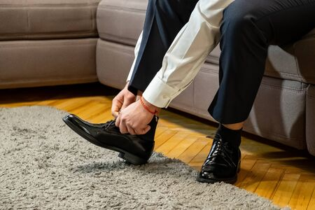 Business man dressing up with classic, elegant shoes. Groom wearing on wedding day, tying the laces and preparing.