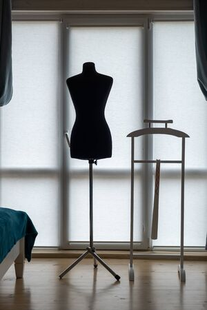 Classic female mannequin silhouette set and stand for clothes in the room on the background of the window.