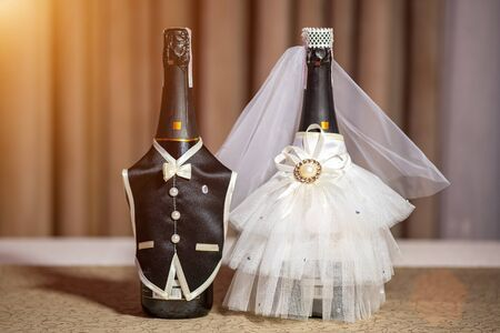 Wedding bottles of Champagne beautifully decorated like bride and groom standing together on wedding table.