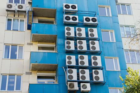 Wall with many air conditioners.