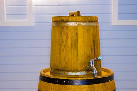 Small and large beer barrels in the Studio on a blue background.