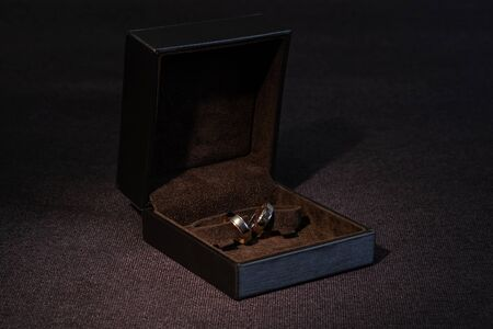 Two gold wedding rings in a brown box on a dark background. 版權商用圖片