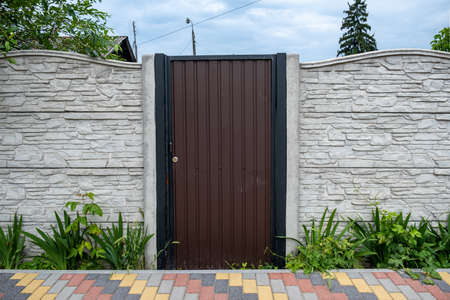 The brown gate of corrugated iron between the concrete slabs of the fence. 스톡 콘텐츠