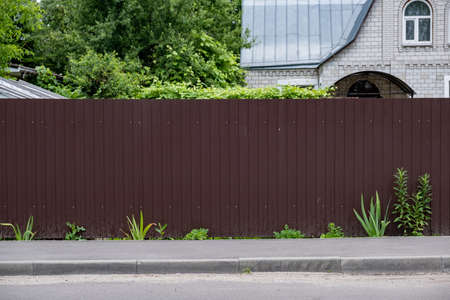 Red metal corrugated fence in front of a residential building. Texture of profiled metal.