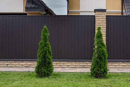 Modern brown corrugated iron fence with decorative brick columns. 스톡 콘텐츠