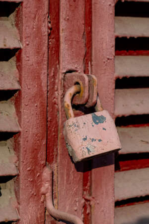 old red padlock covered with rust on the red door.