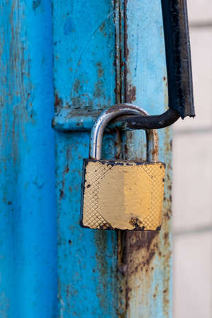 old gold padlock covered with rust on a blue door.