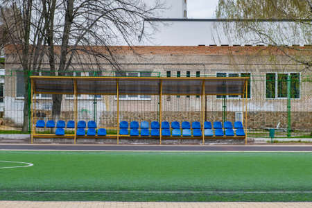 Sports bench on the school soccer field in front of a green fence Stock Photo