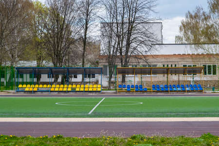 Sports bench on the school soccer field in front of a green fence 版權商用圖片