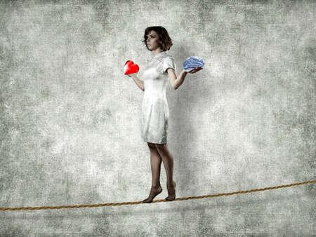 lógica: La muchacha va en una cuerda con un cerebro y el corazón en las manos Foto de archivo
