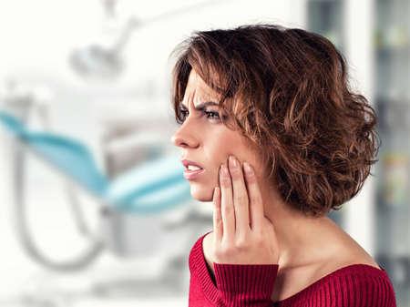 dolor  de diente: La muchacha con un diente doloroso en un consultorio m�dico