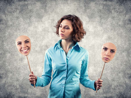 Two masks with different emotions in hands of the girl Stock Photo