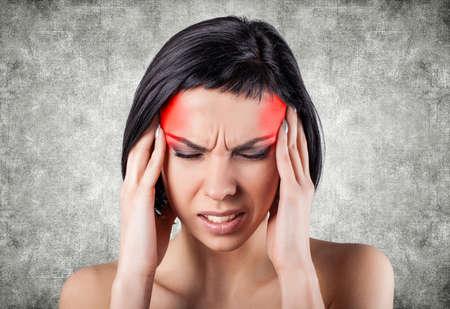 Mädchen mit einer schmerzhaften Kopf auf einem grauen Hintergrund