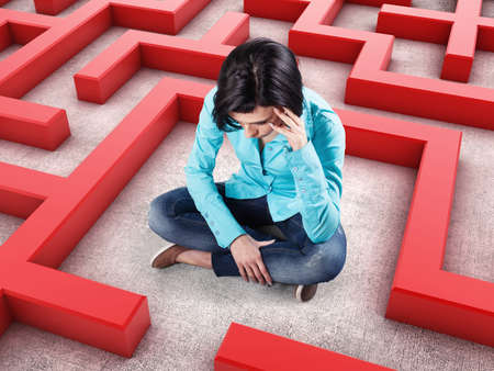 Sad girl sits in a labyrinth with red walls Stock Photo